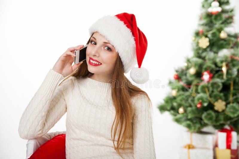 Muchacha en teléfono de la llamada del sombrero de santa por el árbol de navidad fotos de archivo libres de regalías