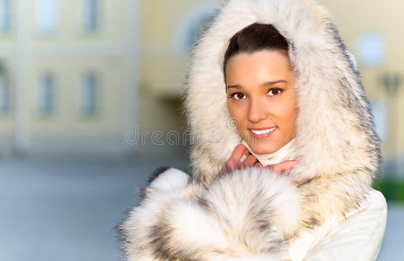 Muchacha en un abrigo de pieles blanco fotografía de archivo