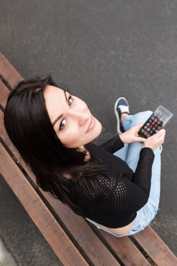 Muchacha en un banco con su teléfono foto de archivo