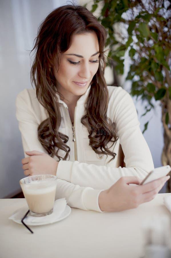 Muchacha en un café con un teléfono en su mano fotografía de archivo