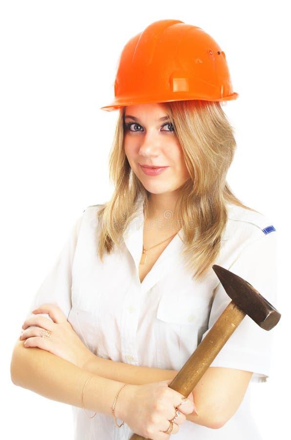 Muchacha en un casco anaranjado con el martillo, aislado imagen de archivo libre de regalías