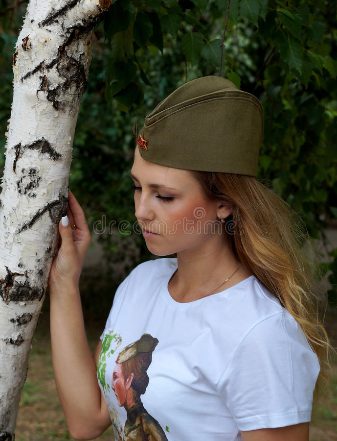 Muchacha en un casquillo de guarnición militar sobre un abedul imagen de archivo