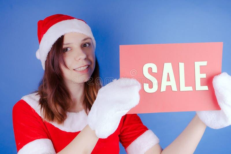 Muchacha en un ` de Santa Claus del ` del traje con una muestra en un fondo azul El concepto de descuentos y de ventas para la Na foto de archivo