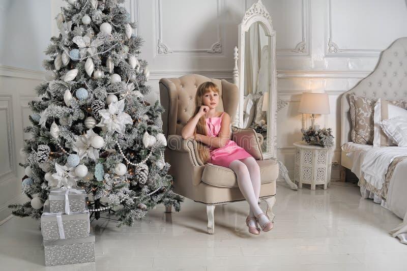 Muchacha en un pálido - vestido rosado que se sienta en una silla en el árbol de navidad imagen de archivo