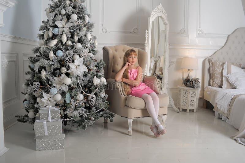 Muchacha en un pálido - vestido rosado que se sienta en una silla en el árbol de navidad imagen de archivo libre de regalías