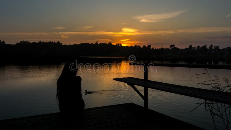 Muchacha en un puente durante puesta del sol foto de archivo