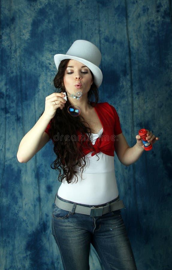 Muchacha en un sombrero blanco con las burbujas de jabón en un fondo azul imagen de archivo