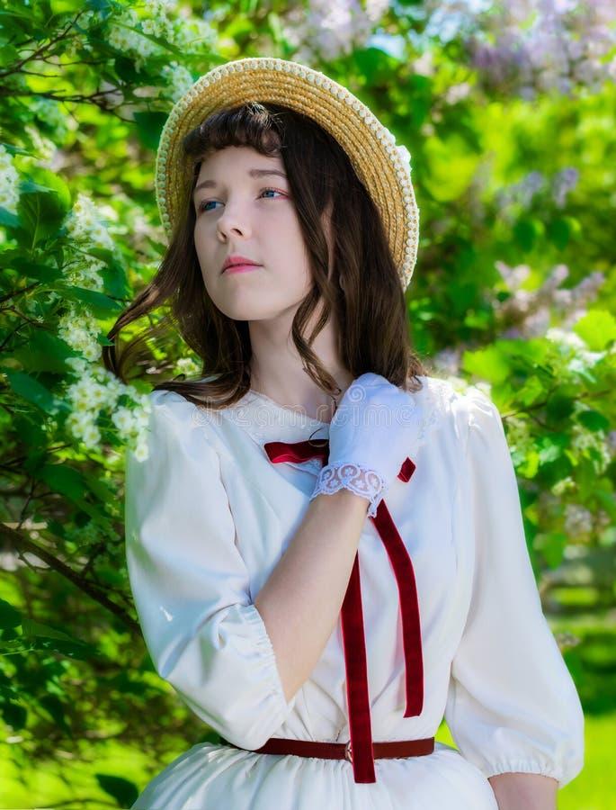 Muchacha en un sombrero blanco del vestido y de paja cerca del espino de las flores imagen de archivo