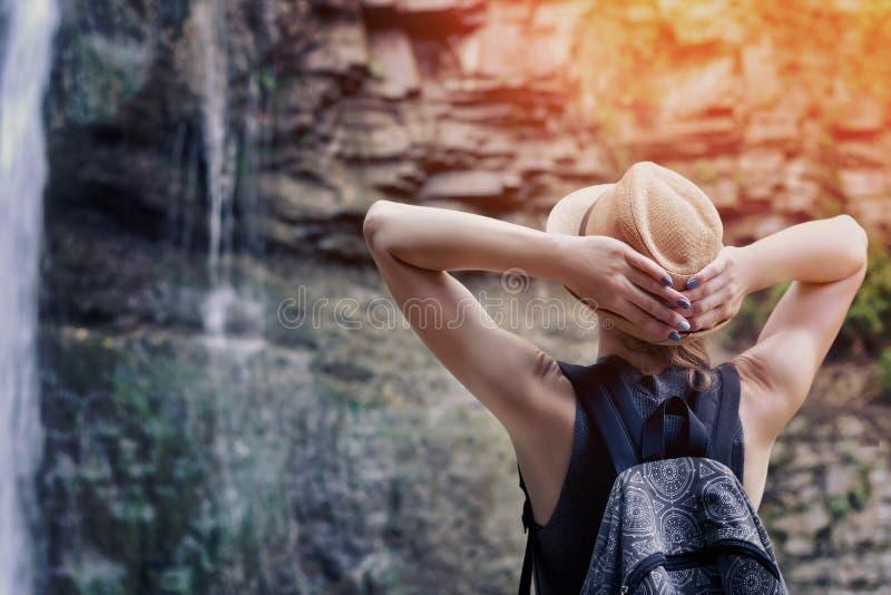Muchacha en un sombrero con la mochila que mira una cascada Manos detrás de la cabeza Visión desde la parte posterior imagen de archivo