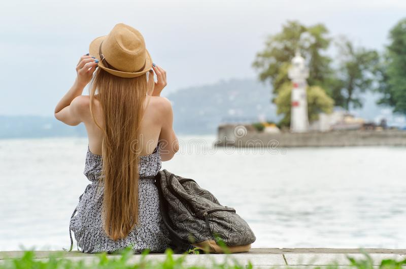 Muchacha en un sombrero con una mochila que se sienta en el embarcadero Montañas y faro en el fondo Visión desde la parte posteri imagen de archivo