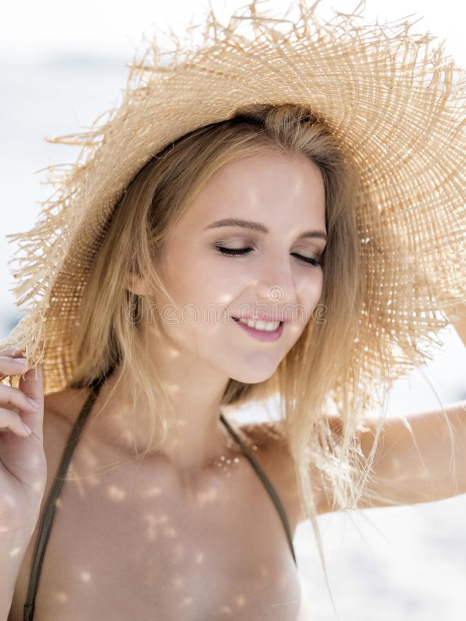 Muchacha en un sombrero de paja en la playa fotos de archivo