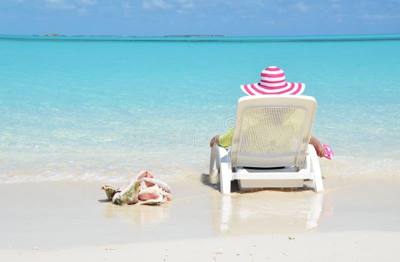 Muchacha en un sombrero rayado en la playa imagenes de archivo