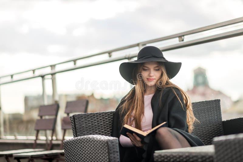 Muchacha en un sombrero y una capa de ala ancha negros que lee un libro en la terraza del restaurante imagen de archivo
