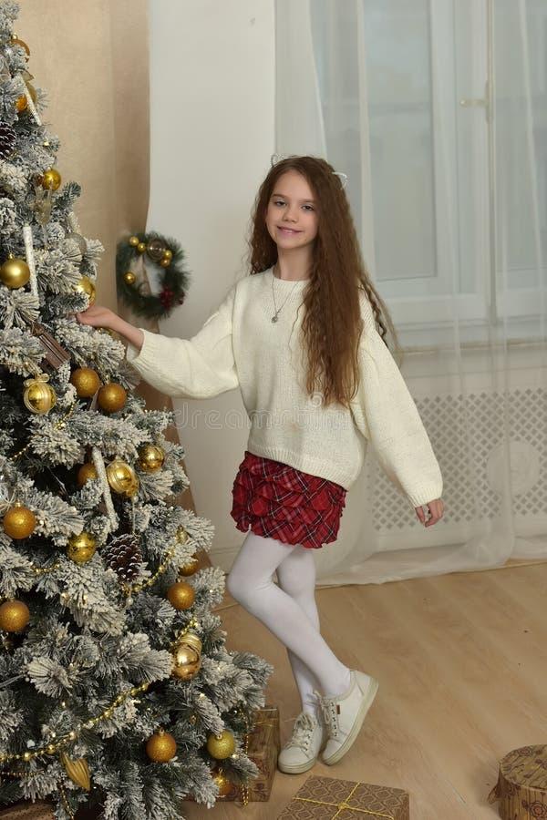 muchacha en un suéter blanco cerca del árbol de navidad imagenes de archivo