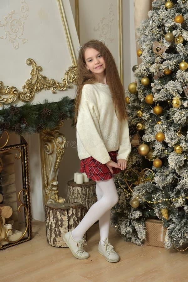 muchacha en un suéter blanco cerca del árbol de navidad foto de archivo