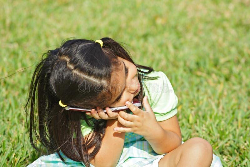 Muchacha en un teléfono celular imagen de archivo