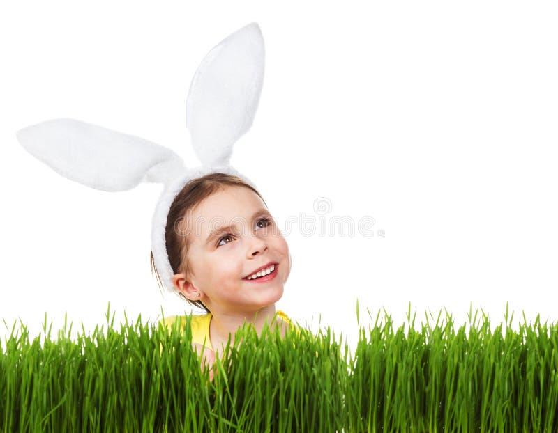 Muchacha en un traje del conejo que mira para arriba contra un fondo de la hierba verde y del fondo blanco fotos de archivo