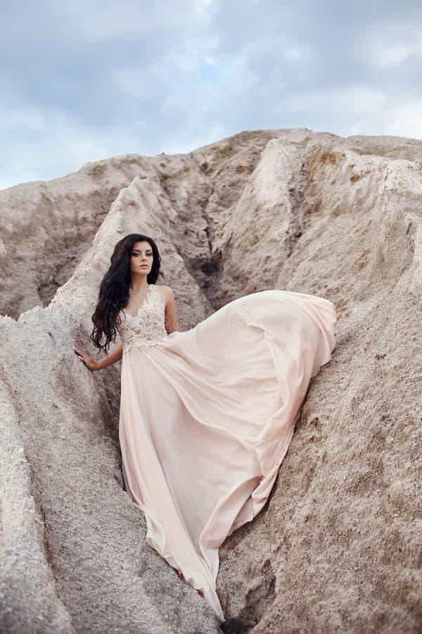 Muchacha en un vestido azul claro que coloca en el viento con las montañas i fotografía de archivo