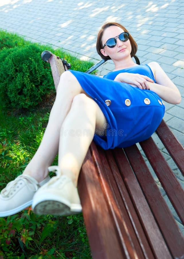 Muchacha en un vestido azul largo que miente en un banco en la calle de la ciudad, descansando y divirtiéndose foto de archivo libre de regalías
