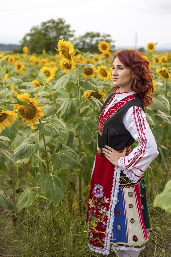 Muchacha en un vestido búlgaro tradicional en un campo de girasoles imagen de archivo libre de regalías