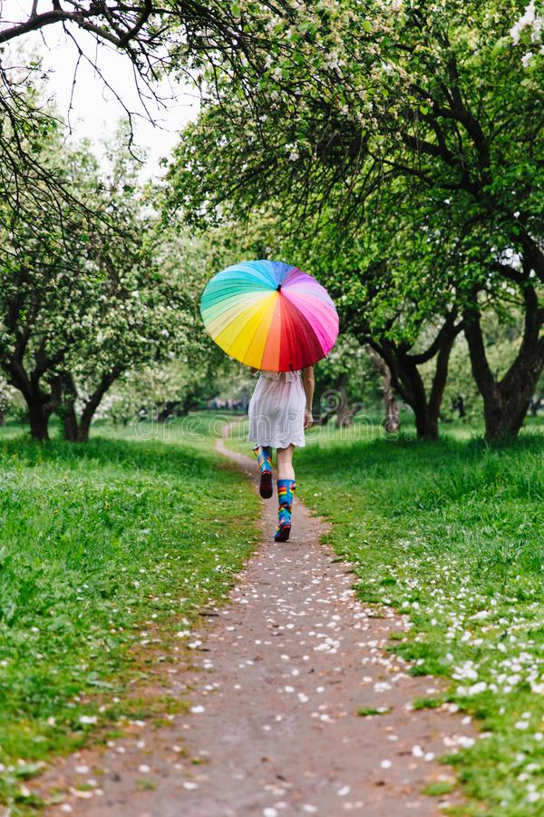 Muchacha en un vestido blanco que salta en el jardín floreciente con el arco iris-paraguas colorido Primavera, al aire libre imagen de archivo