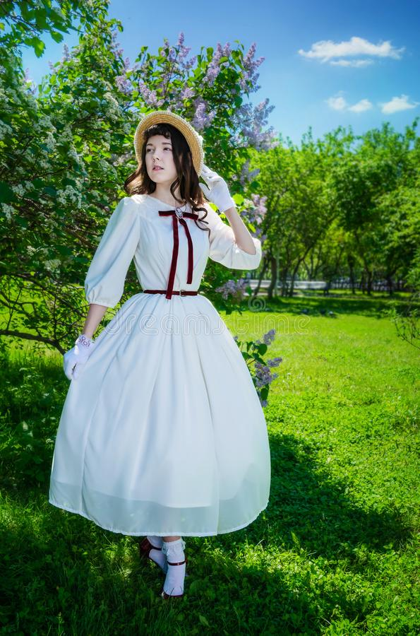 Muchacha en un vestido blanco y paseos del sombrero de paja imágenes de archivo libres de regalías