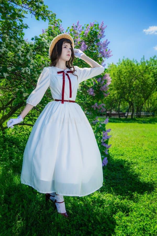 Muchacha en un vestido blanco y paseos del sombrero de paja imagenes de archivo