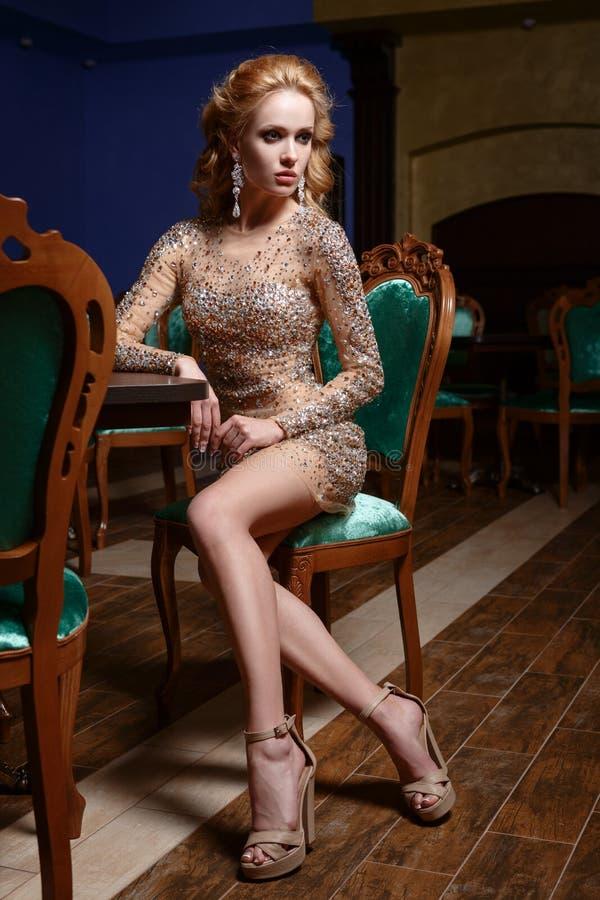 Muchacha en un vestido brillante, sentándose en un pasillo lujoso de la silla verde imágenes de archivo libres de regalías
