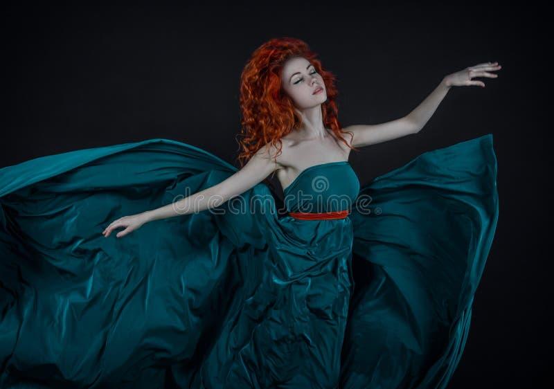 Muchacha en un vestido de seda, un baile pelirrojo hermoso de la muchacha en un vuelo del vestido del verde largo en el aire, un  foto de archivo libre de regalías
