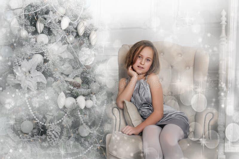 Muchacha en un vestido gris pálido que se sienta en una silla en el árbol de navidad fotos de archivo