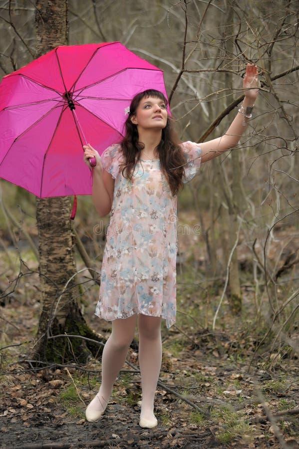 Muchacha en un vestido ligero con un paraguas rosado en el parque fotos de archivo libres de regalías