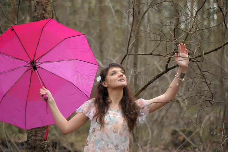 Muchacha en un vestido ligero con un paraguas rosado en el parque fotos de archivo
