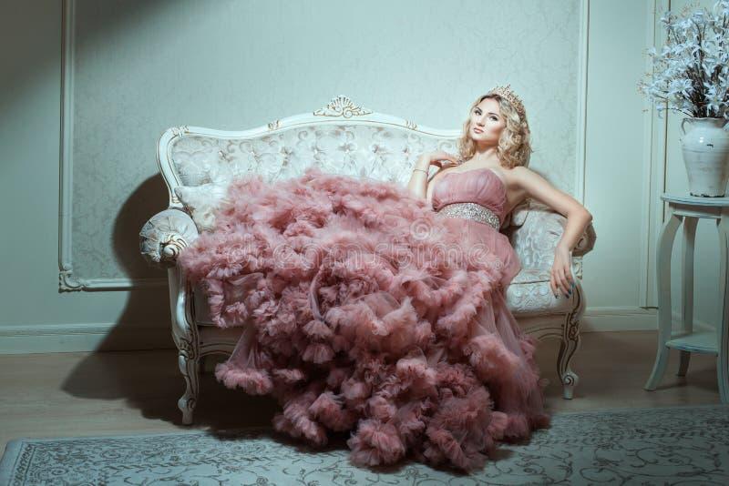 Muchacha en un vestido magnífico que se sienta en el sofá imagenes de archivo
