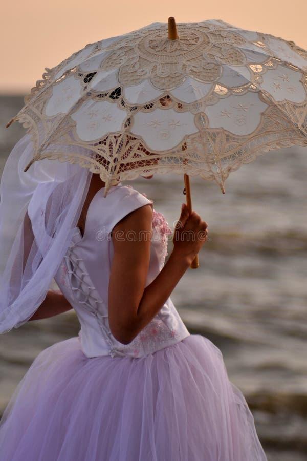 Muchacha en un vestido que se casa debajo de un paraguas a cielo abierto fotos de archivo