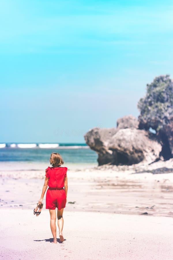 Muchacha en un vestido rojo que camina descalzo en la orilla de mar Playa tropical, isla de Bali Día asoleado foto de archivo