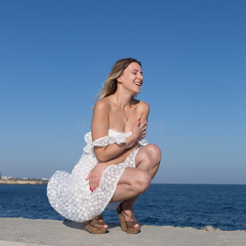 Muchacha en un vestido sin mangas blanco corto en orilla del mar imágenes de archivo libres de regalías