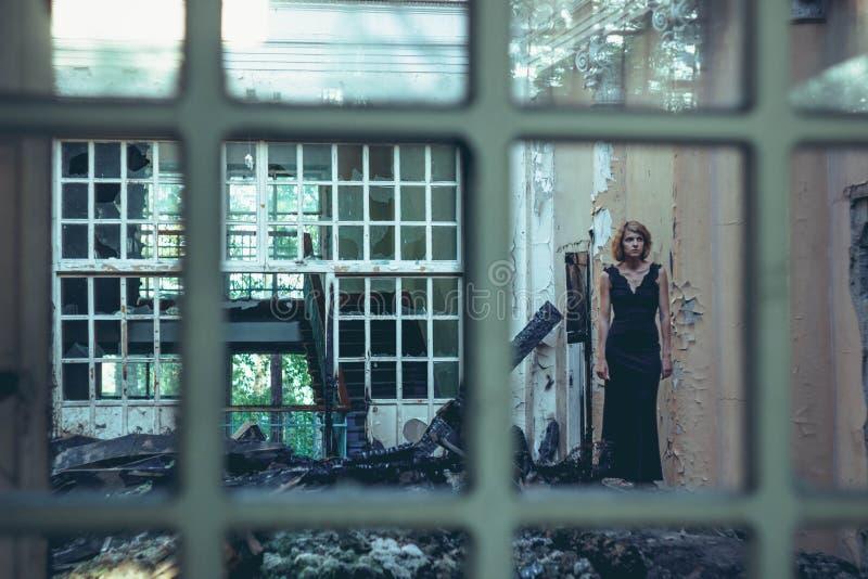 Muchacha en un vestido en una casa vieja foto de archivo
