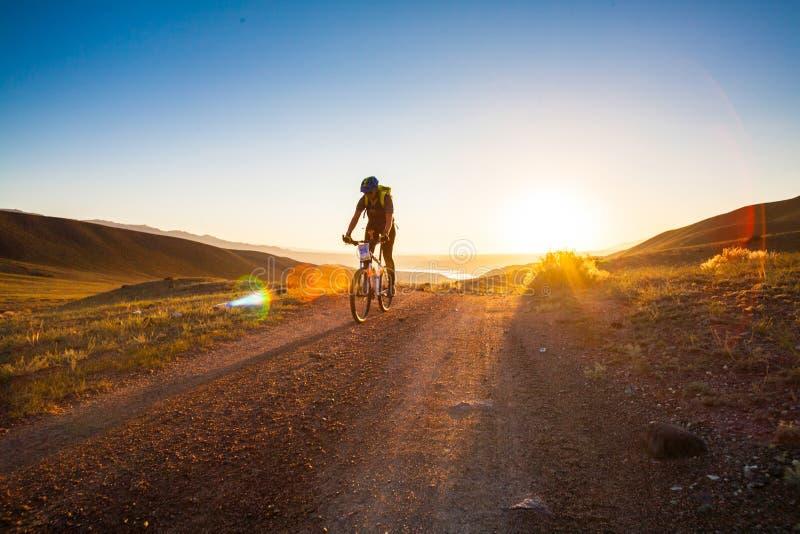 Muchacha en una bicicleta en los rayos del sol naciente fotografía de archivo libre de regalías