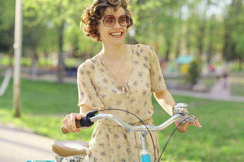 Muchacha en una bicicleta en vestido imágenes de archivo libres de regalías