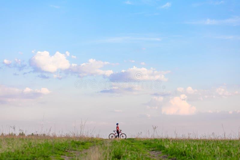 Muchacha en una bicicleta en un fondo del cielo azul y de la hierba verde fotografía de archivo