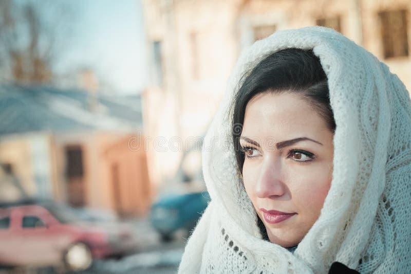 Muchacha en una bufanda blanca en su cabeza Ascendente cercano de la muchacha Una mujer ata una bufanda sobre su cabeza imagenes de archivo