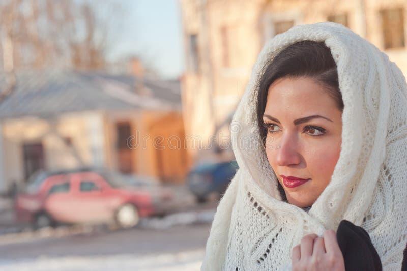 Muchacha en una bufanda blanca en su cabeza Ascendente cercano de la muchacha Una mujer ata una bufanda sobre su cabeza imagen de archivo