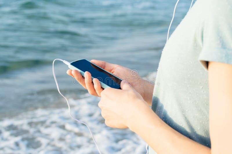 Muchacha en una camisa azul que lleva a cabo un teléfono móvil disponible y el listenin imagenes de archivo