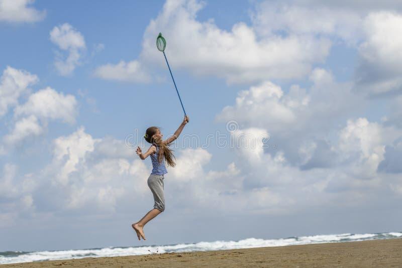 Muchacha en una camiseta adentro rayada en las nubes de las capturas del mar imagen de archivo