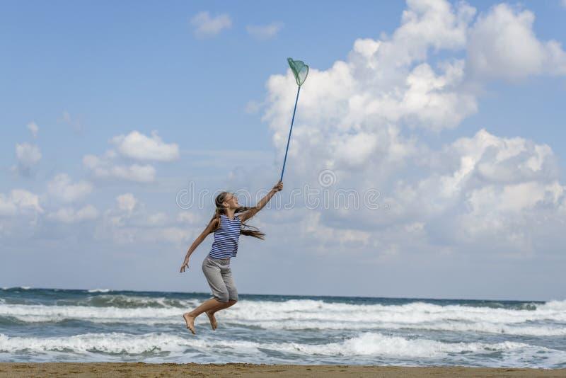 Muchacha en una camiseta adentro rayada en las nubes de las capturas del mar fotos de archivo libres de regalías