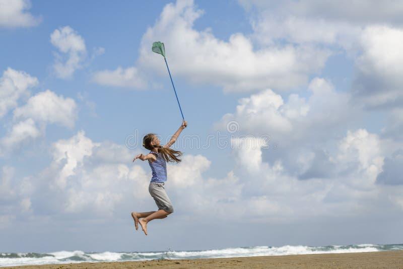 Muchacha en una camiseta adentro rayada en las nubes de las capturas del mar fotos de archivo