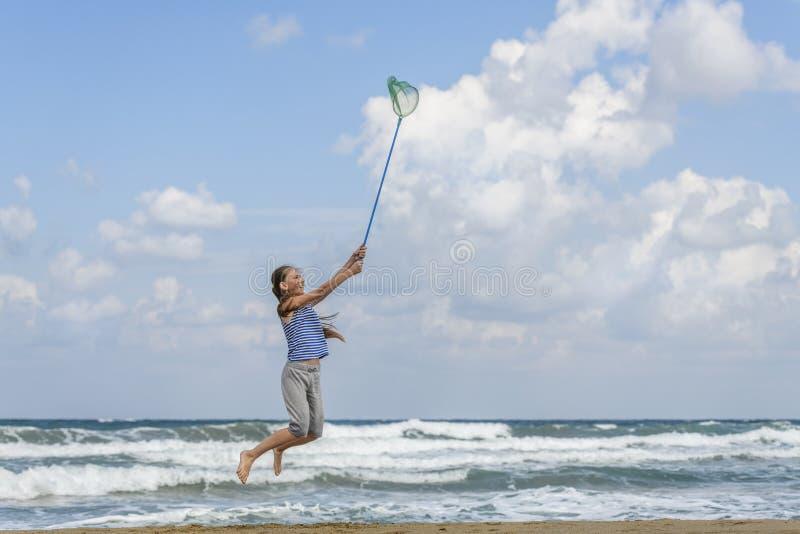 Muchacha en una camiseta adentro rayada en las nubes de las capturas del mar imagenes de archivo