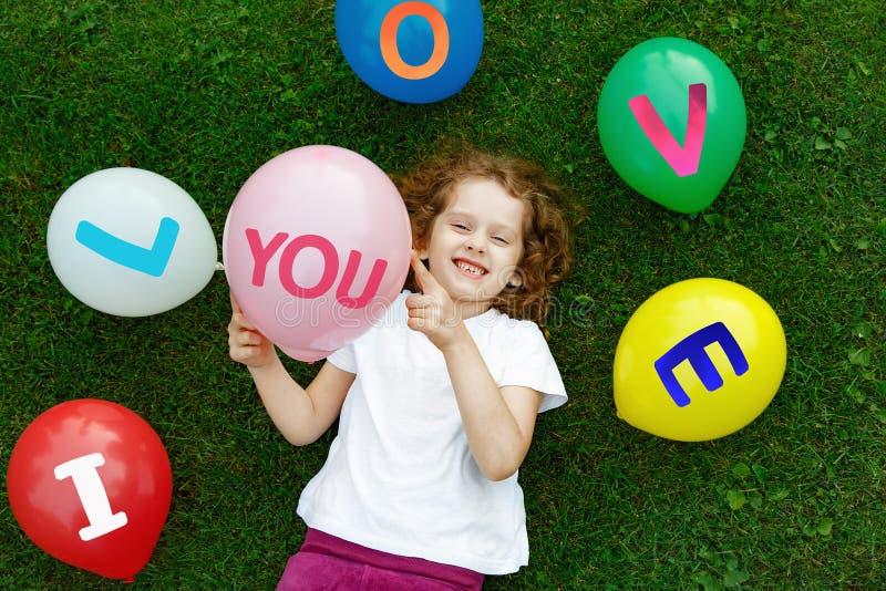 Muchacha en una camiseta blanca que sostiene un globo coloreado fotos de archivo