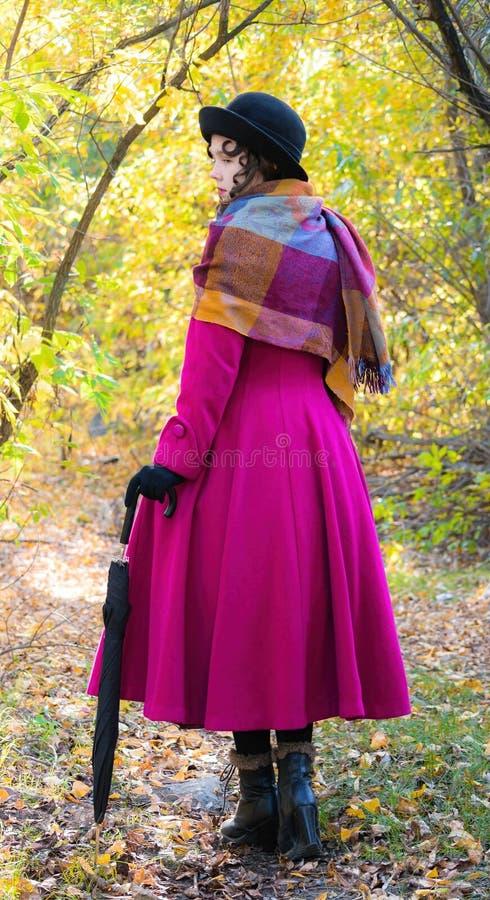 Muchacha en una capa carmesí brillante que camina en día soleado del otoño del bosque imagenes de archivo
