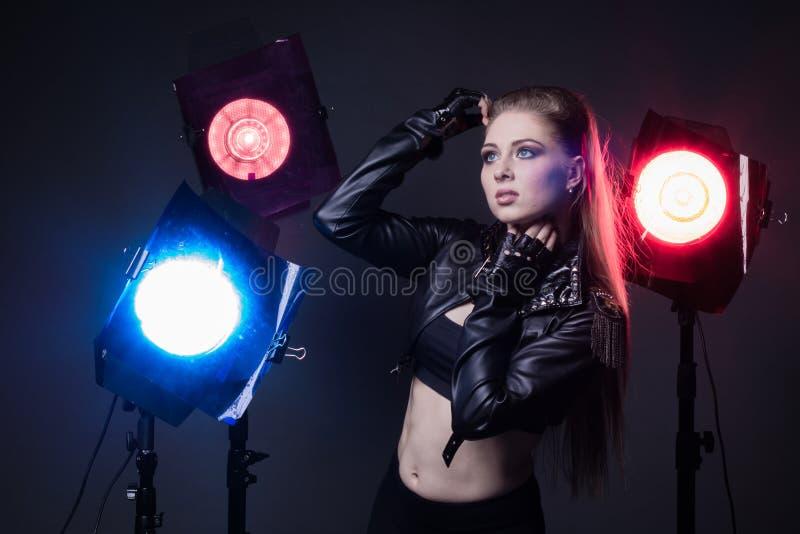 Muchacha en una chaqueta de cuero en etapa y proyectores coloreados imagenes de archivo